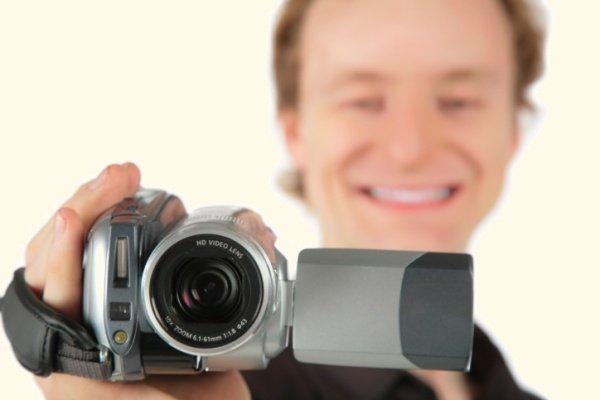 Мужчина держит видеокамеру в руках