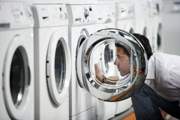 Мужчина смотрит стиральные машины